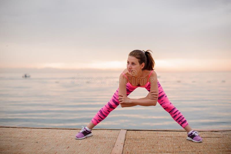 Menina feliz que faz exercícios do estiramento no nascer do sol perto do mar imagem de stock