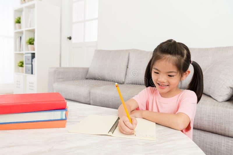 Menina feliz que faz o estudo dos trabalhos de casa da escola imagens de stock