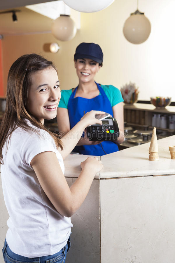 Menina feliz que faz o pagamento de NFC quando empregada de mesa Smiling imagem de stock royalty free