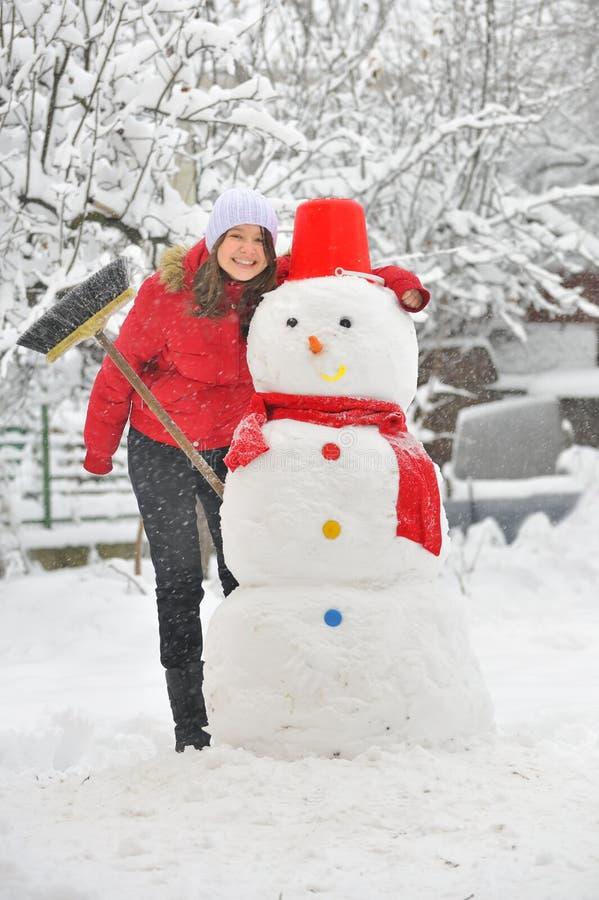 Menina feliz que faz um boneco de neve imagem de stock