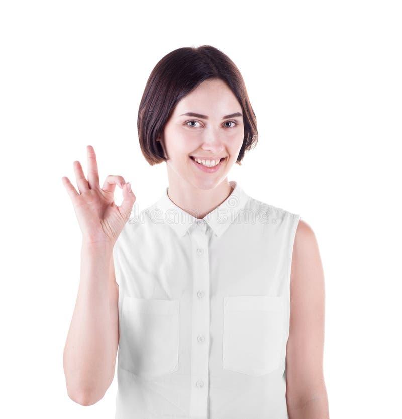 Menina feliz que faz um sinal APROVADO Uma mulher de sorriso em uma camisa leve isolada em um fundo branco Uma menina bonito com  fotos de stock