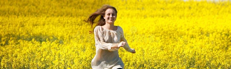 Menina feliz que funciona no campo de flor amarelo imagem de stock