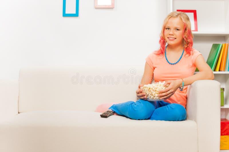 Menina feliz que guarda a bacia com pipoca no sofá branco fotografia de stock royalty free