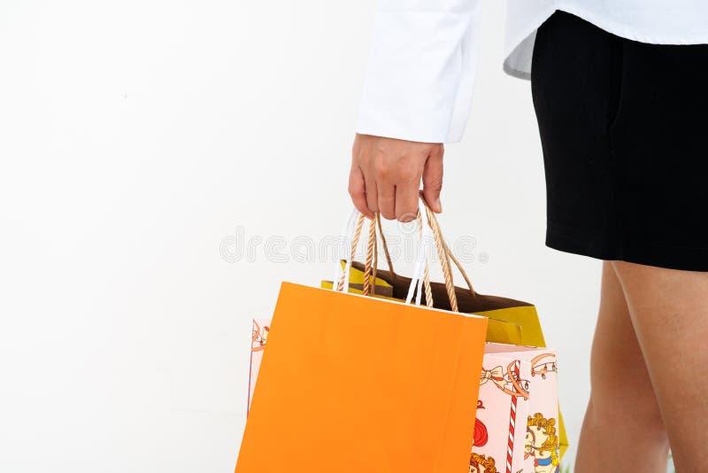 Menina feliz que guarda o saco de compras colorido para o presente do ano novo da família no fundo branco imagem de stock