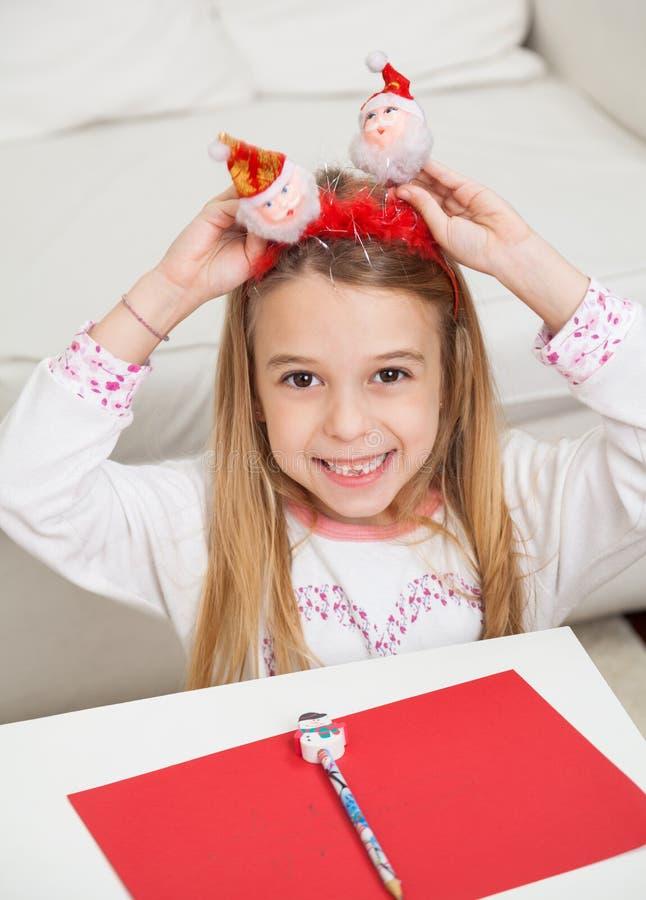 Menina feliz que guarda Santa Headband fotografia de stock royalty free