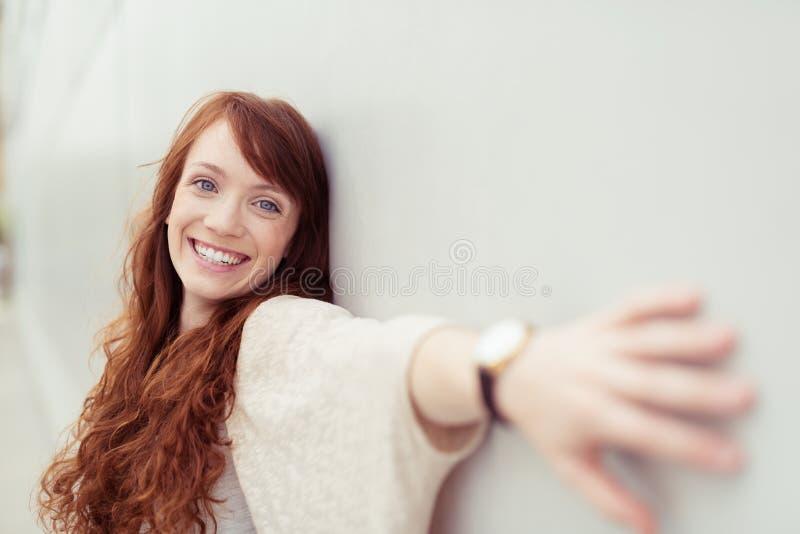 Menina feliz que inclina-se na parede com braços dentro lateralmente fotografia de stock
