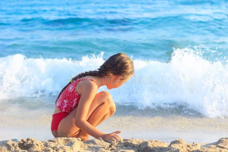 A menina feliz que joga com a areia pelo mar acena verão SU imagens de stock