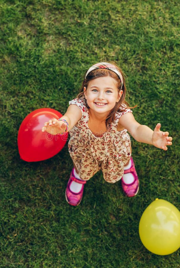 Menina feliz que joga com balões coloridos fotografia de stock royalty free