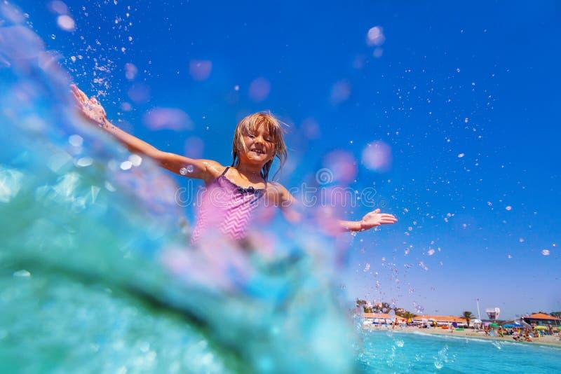 Menina feliz que joga em ondas de água pouco profunda fotos de stock