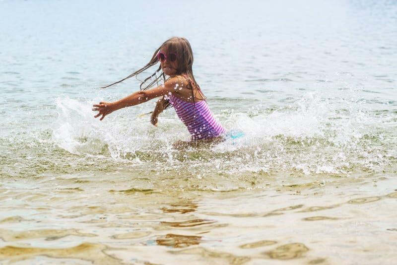 Menina feliz que joga em ondas de água pouco profunda Menina feliz imagens de stock royalty free