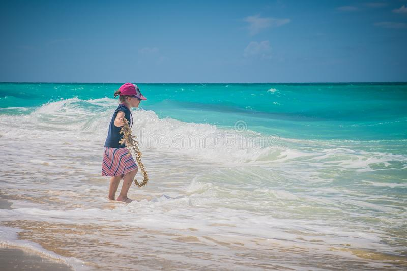 Menina feliz que joga na praia Feriado, fora imagem de stock