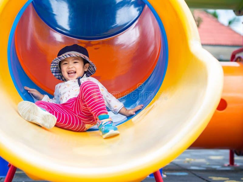 Menina feliz que joga no campo de jogos Crianças, felizes, fá imagem de stock