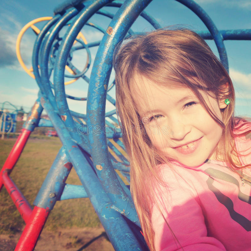 Menina feliz que joga no campo de jogos - efeito de Instagram fotografia de stock royalty free