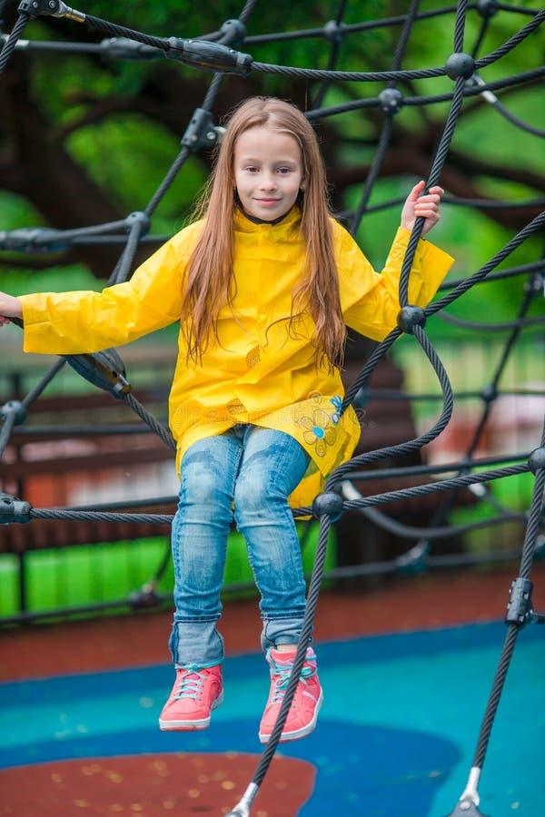 Menina feliz que joga no campo de jogos exterior no dia do outono fotos de stock