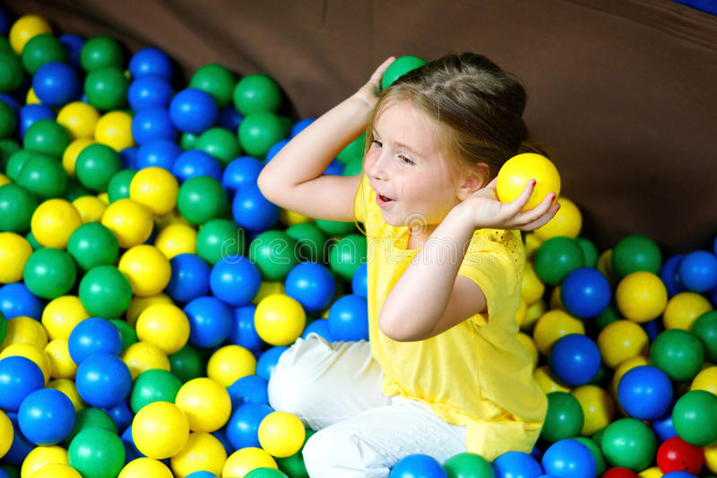 Menina feliz que joga no campo de jogos plástico colorido das bolas foto de stock