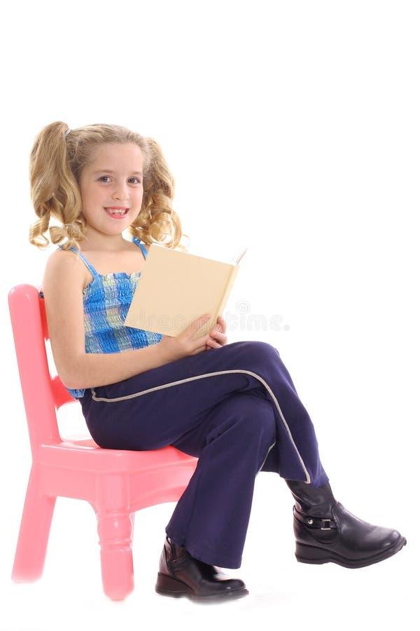 Menina feliz que lê um livro imagem de stock