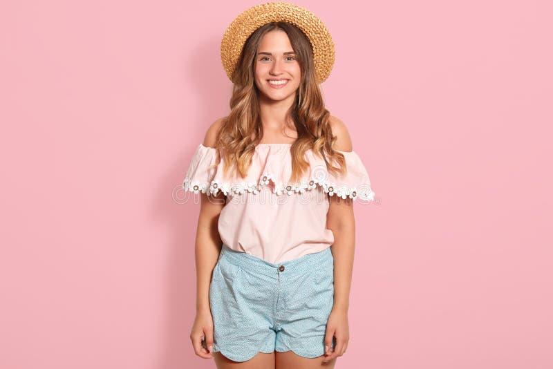 A menina feliz que levanta no chapéu de palha, aumentou blusa do verão e curto azul A mulher bonita tem o sorriso de encantamento imagens de stock royalty free