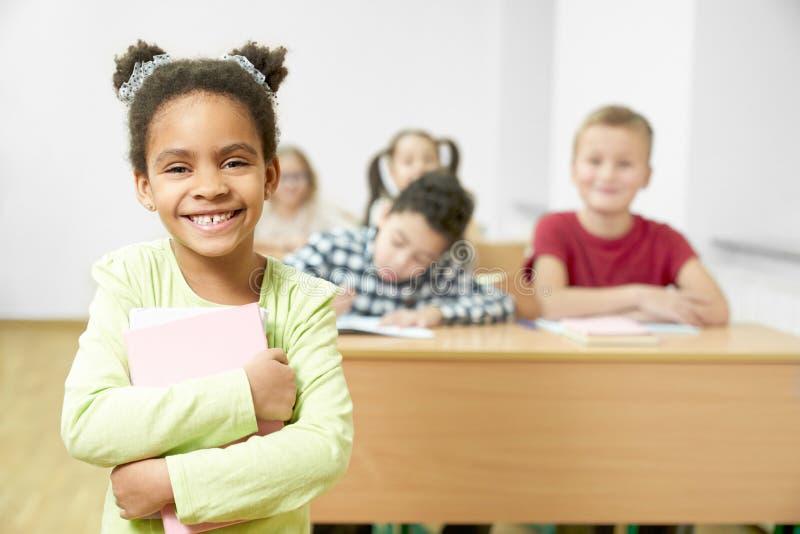 Menina feliz que mantém livros nas mãos e que levanta na sala de aula fotos de stock royalty free