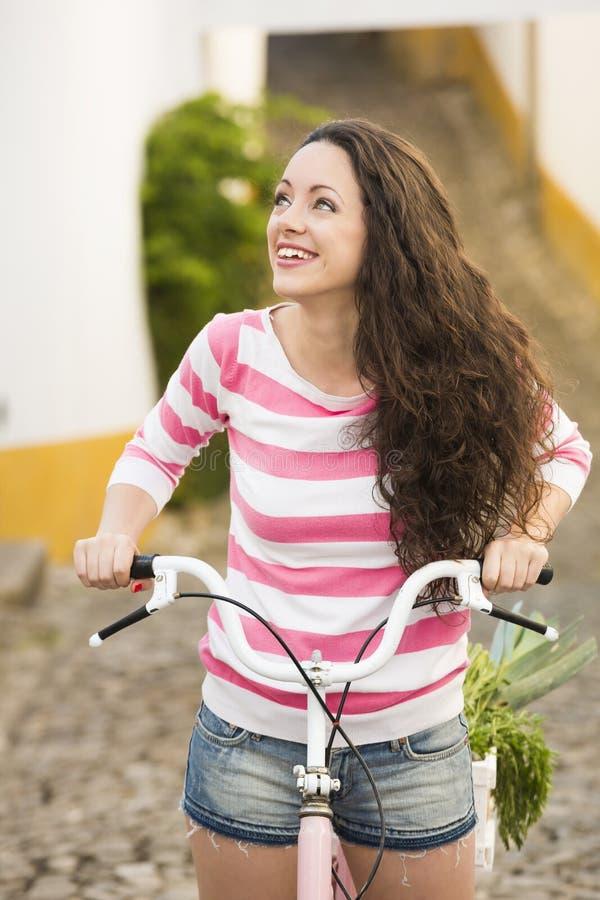 Menina feliz que monta uma bicicleta imagem de stock