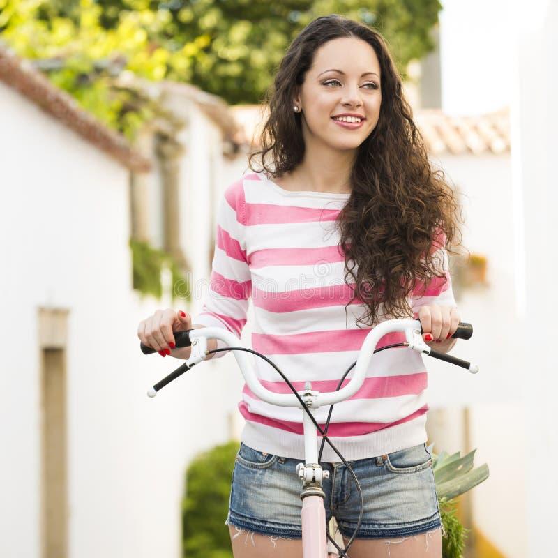 Menina feliz que monta uma bicicleta fotos de stock