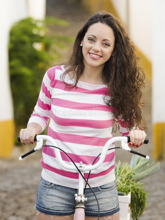 Menina feliz que monta uma bicicleta foto de stock