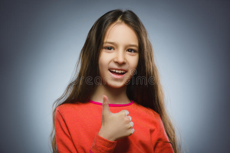 Menina feliz que mostra o thub acima Sorriso da criança do retrato do close up isolado no cinza imagens de stock royalty free