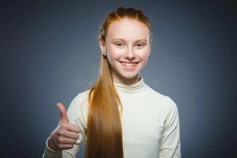 Menina feliz que mostra o thub acima Sorriso da criança do retrato do close up isolado no cinza imagens de stock