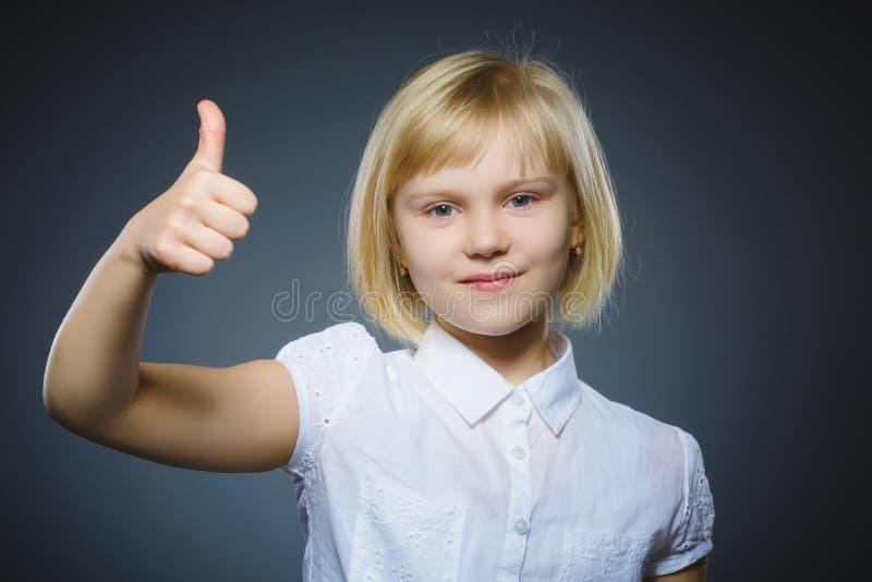 Menina feliz que mostra thubs acima Criança do retrato do close up que sorri no cinza imagens de stock royalty free