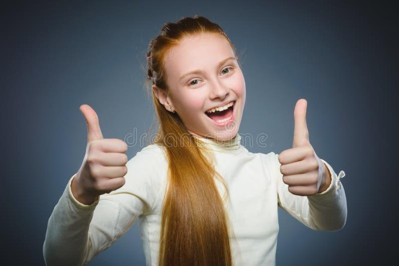 Menina feliz que mostra thubs acima Sorriso da criança do retrato do close up isolado no cinza imagem de stock royalty free