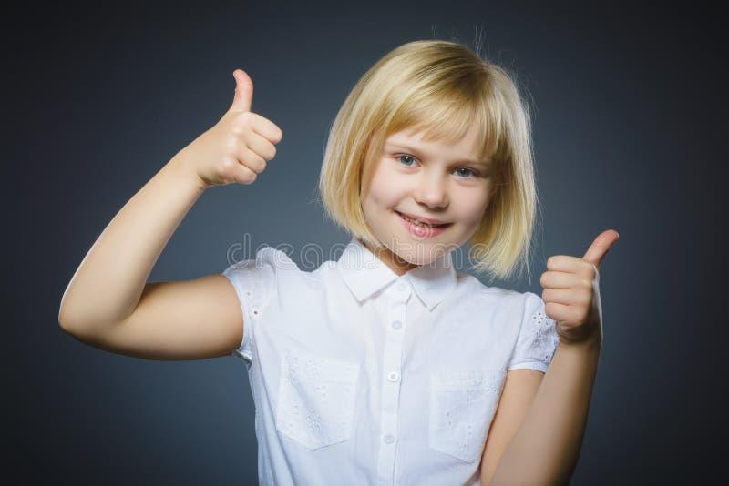 Menina feliz que mostra thubs acima Sorriso da criança do retrato do close up isolado no cinza fotos de stock