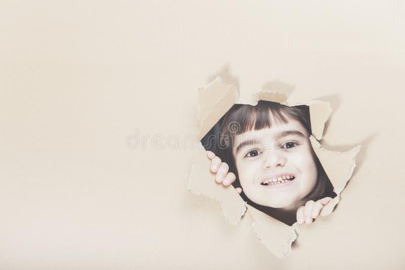 Menina feliz que olha através de um furo de papel foto de stock