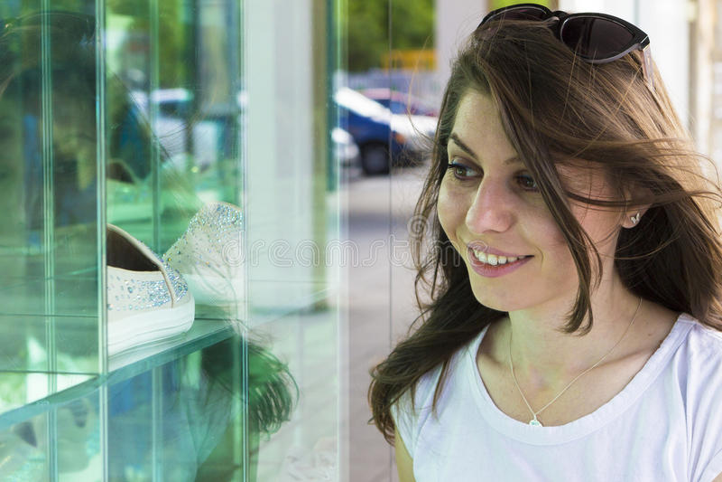Menina feliz que olha na janela da loja imagem de stock