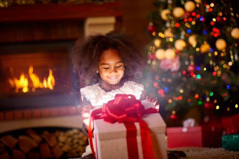 Menina feliz que olha no presente de Natal mágico aberto foto de stock royalty free