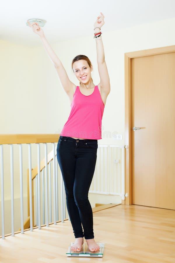 Menina feliz que pesa-se na escala de banheiro fotografia de stock royalty free