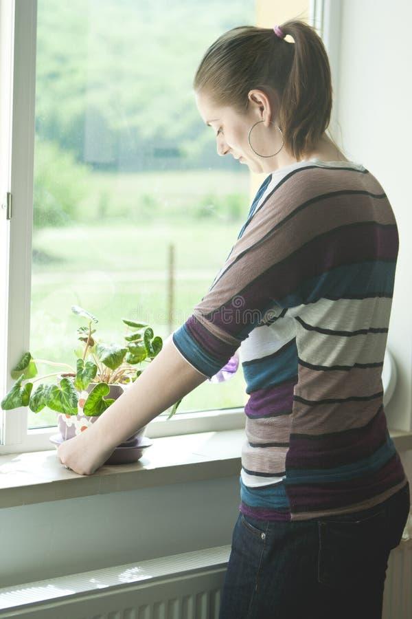 Menina feliz que pulveriza uma planta no potenciômetro imagens de stock royalty free