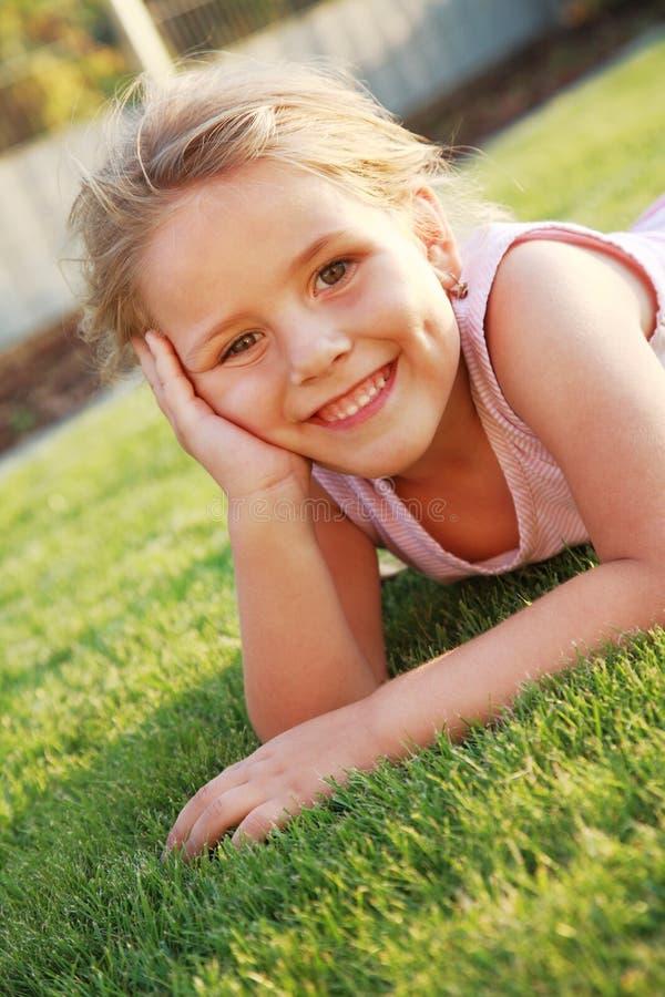 Menina feliz que relaxa em uma grama foto de stock
