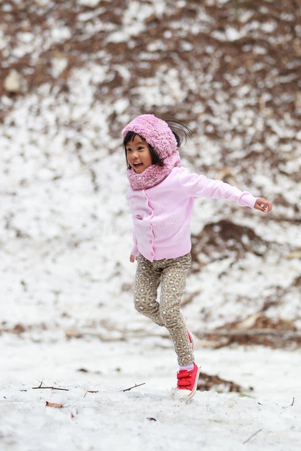 Menina feliz que salta na neve foto de stock royalty free