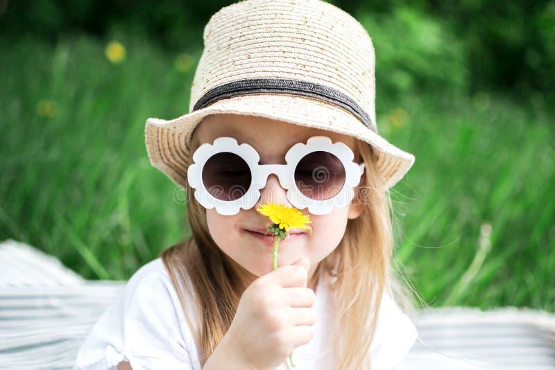 Menina feliz que senta-se na grama verde com o dente-de-leão da flor em suas mãos fotografia de stock