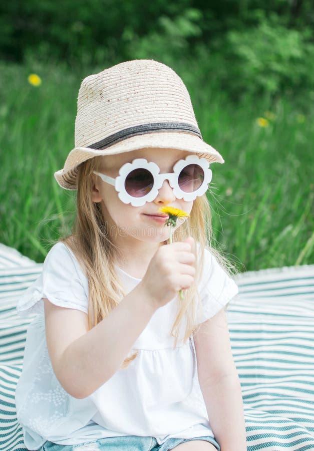 Menina feliz que senta-se na grama verde com o dente-de-le?o da flor em suas m?os fotografia de stock royalty free
