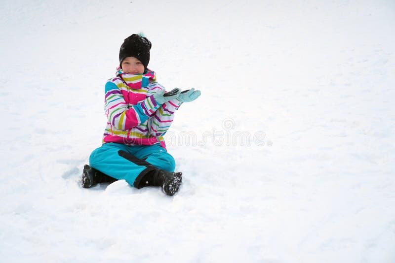 Menina feliz que senta-se na neve no inverno Uma criança em um terno de esqui com suas mãos mostra no espaço da cópia imagem de stock