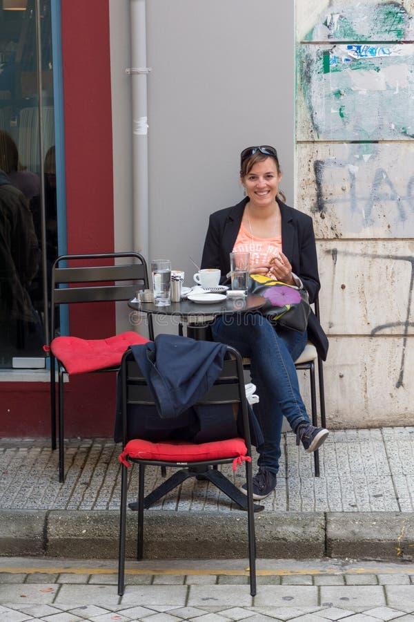 Menina feliz que senta-se no caffe da rua imagens de stock royalty free