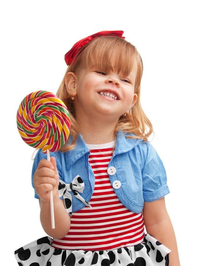 Menina feliz que sorri e que prende o lollipop imagem de stock