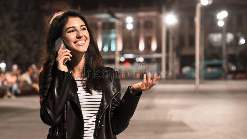 Menina feliz que tem a conversa no telefone, andando no centro de cidade fotografia de stock royalty free