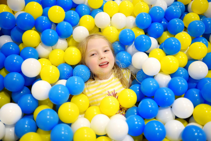 Menina feliz que tem o divertimento no poço da bola no centro interno do jogo das crianças Criança que joga com as bolas colorida fotos de stock