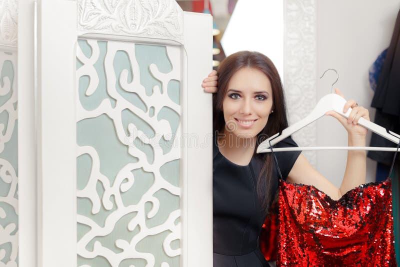 Menina feliz que tenta no vestido de partido vermelho no vestuario fotos de stock