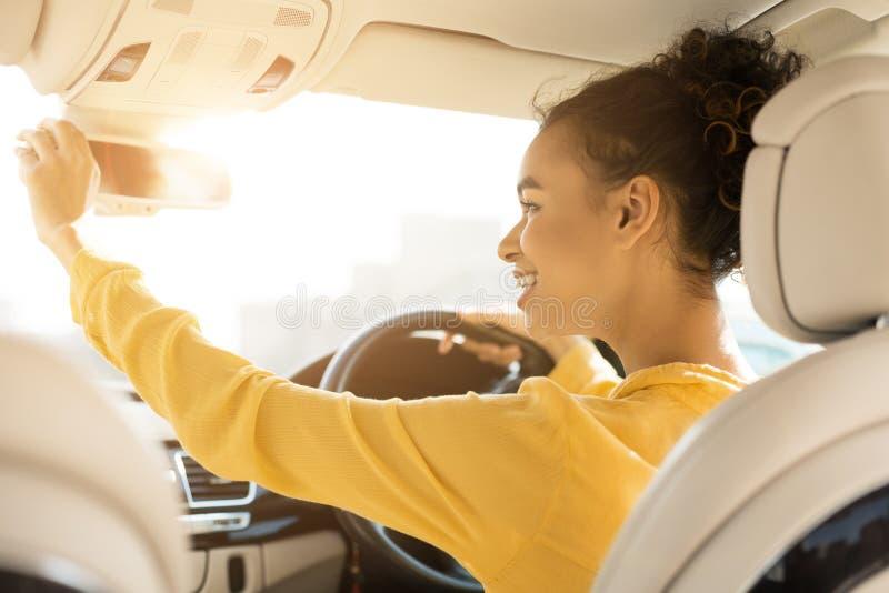 Menina feliz que toca no espelho retrovisor, conduzindo o carro foto de stock