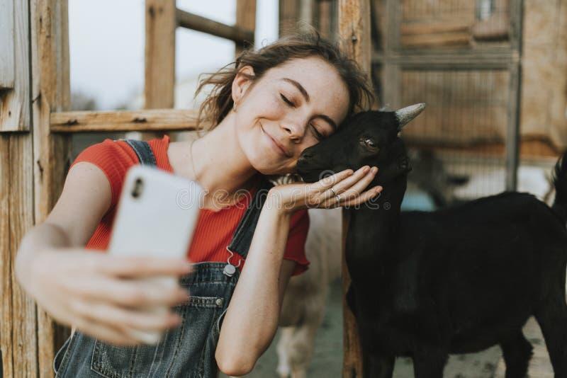 Menina feliz que toma um selfie com uma cabra preta do bebê imagens de stock