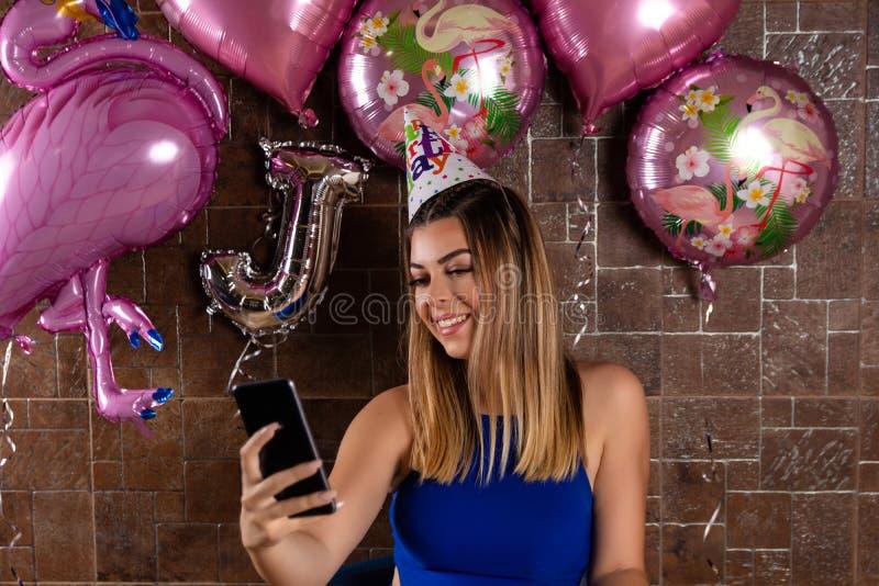 Menina feliz que toma um selfie e que comemora um aniversário com um tampão na cabeça foto de stock royalty free
