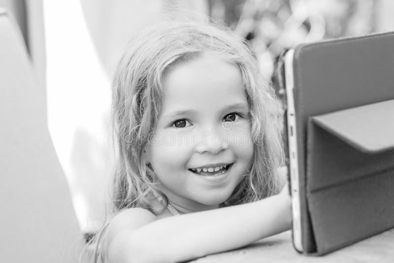 Menina feliz que usa o computador da tabuleta imagem de stock