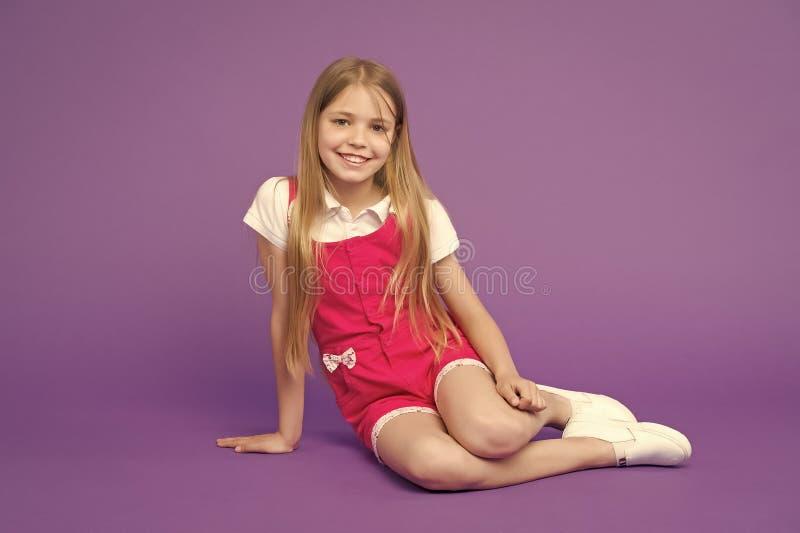 A menina feliz relaxa no fundo violeta olhar da beleza e da forma Criança pequena com sorriso na cara bonito, beleza Forma imagem de stock royalty free